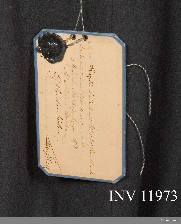 """Grupp C I. Kapott m/1873 av gråmelerat kläde. Dep från  K. Arméförvaltningens Intendentsdep. Vidhängande modellapp med text: """"Modell å kapott av gråmelerat kläde att tjena till efterrättelse enligt generalorder denna dag nr 51. Stockholm den 30 januari 1873. På nådigste befalning O. Weidenhielm. (oläslig underskrift)"""""""