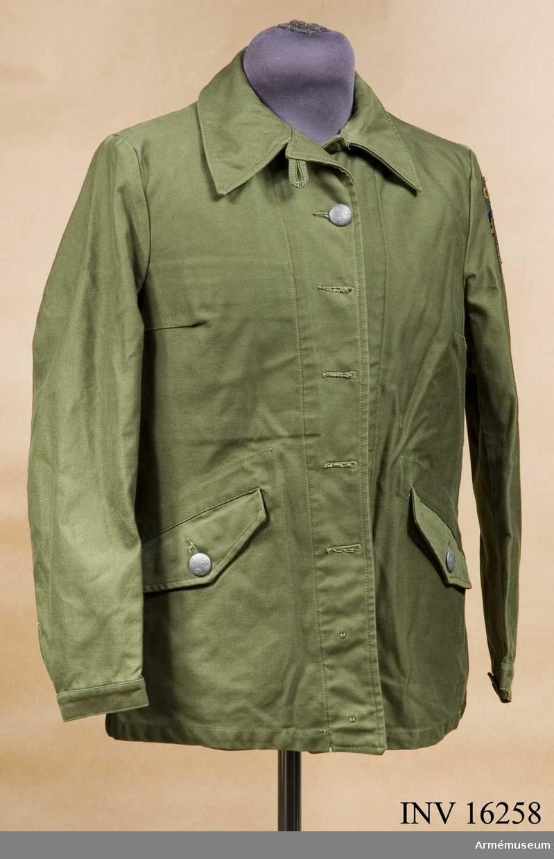 Tillverkad av olivgrönt tyg, är enradig och knäpps med fem stora knappar m/1939, är högknäppt i halsen, har två snedställda sidfickor samt reglerbar ärmlinning. På vänster ärm nationalitetsmärket och under det armétecknet vävt gult.