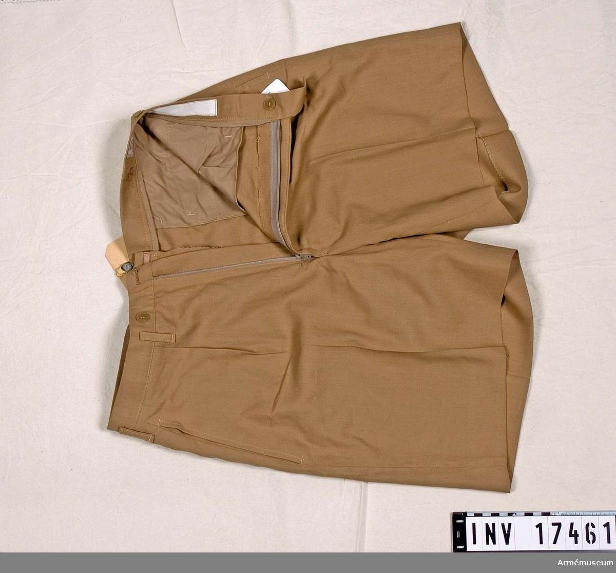 Grupp C I.  Ur tropikuniform m/1961 bestående av skjorta, skjorts, kravatt, livrem, strumpor, skor och basker.