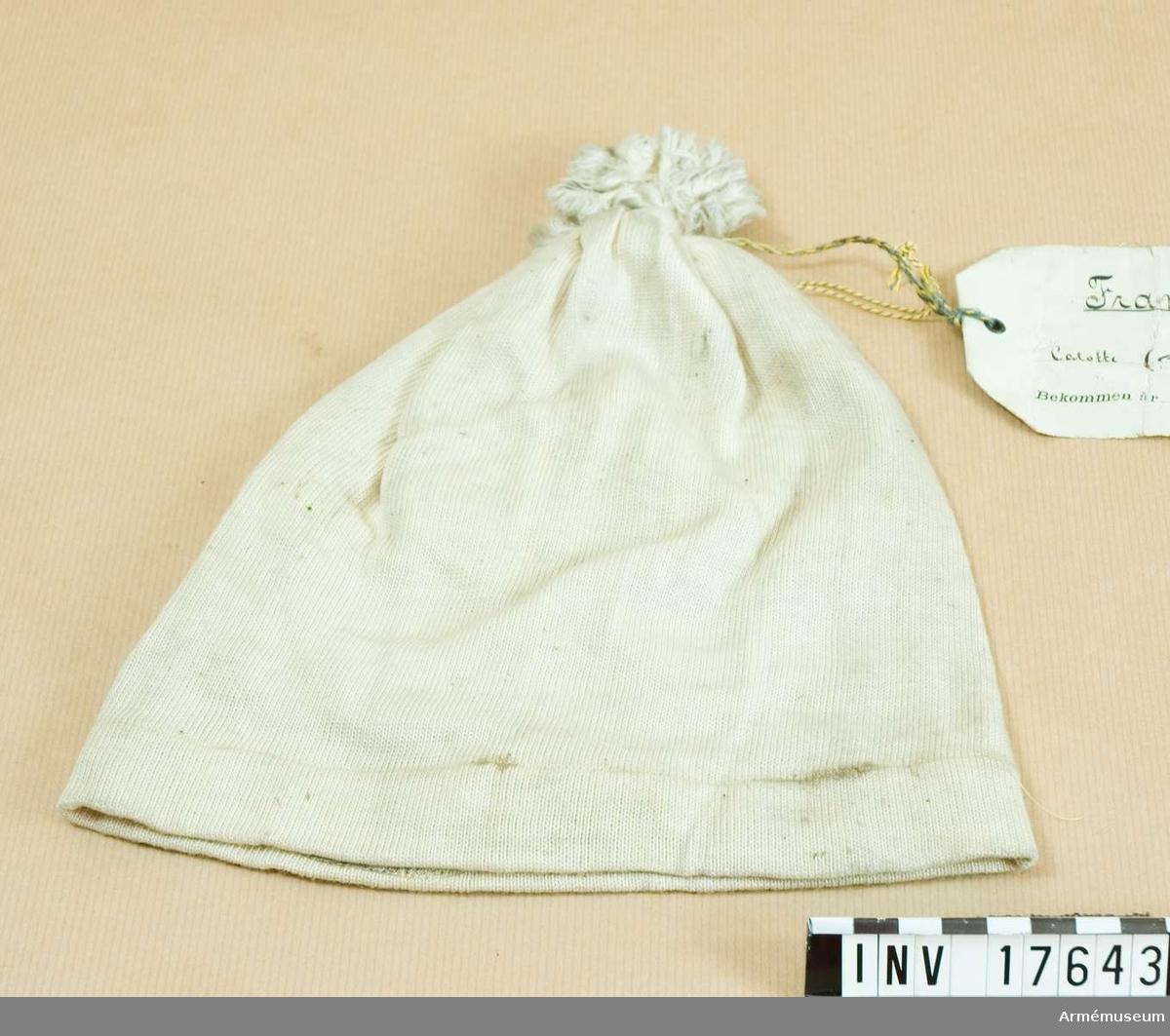 Grupp C I. Nattmössa tillverkad i Frankrike. Nattmössa av vitt bomullstyg med pompong på övre delen av vitt bomullsgarn.