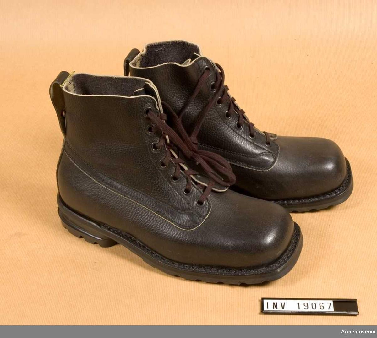 Becksömsydda, svarta skodon i helbesätsmodell med besätsfoder, bakrem och med klack och yttersula av gummi. Snörning i sju hål och med pådragsögla  baktill.