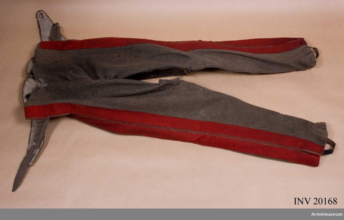 """Grupp C I. Ur uniform m/1820-40 för menig vid Livgardet till häst, Andra regementet 1. Gardets kavalleridivision. Av gråbrunt kläde med dubbla, röda klädeslister med mellan- liggande, röd passpoal på sidorna (lampasse). Byxorna äro försedda med skinnskoning och hällor av läder Foder av grov linnelärft med tryckta ryska bokstäver, initialer för Livgardet t häst (se bilaga). Knäppning i var sida.  LITT  Hanbuch der Uniformenkunde, Knötel/Sieg, sida 323. År 1814 fick kyrassjärregementen i stället för gråbruna byxor med knappar sådana med """"lampasse""""-list i kragens färg. """"Istoria Kavalergardov"""", del IV, sida 5, 19, 89, 106. Del III, sida 211, 256, fotografier och ritningar."""