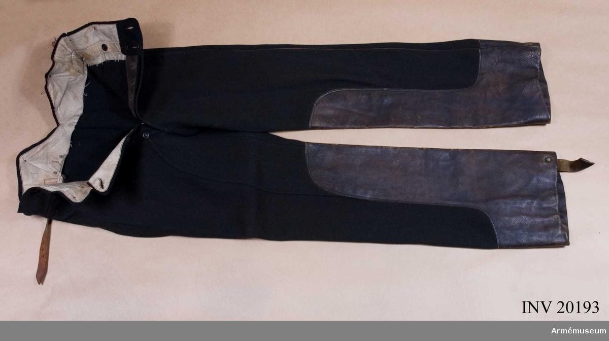 """Grupp C I. Ur uniform för menig vid Livgardets artilleribrigad. För """"bombadir"""" (korpral). 1812-1817. Byxor (benläder) av svart läder med tio flata mässingsknappar. Knapparna fästa med öglor vid byxorna. Öglorna går genom lädret och en smal rem som går genom den, fäster knapparna vid byxorna En hälla är fastsydd vid det ena byxbenet. Smal, röd passpoil och skinnskodda nedtill."""