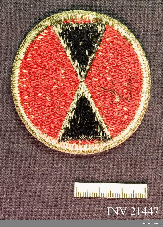 Samhörande gåva: 21437-51, 22351-2, uniformsemblem.Emblem, 7th Infantry Division. Grupp C I. För amerikansk trupp som deltog i striderna i Korea 1950-53. USA 7th Infantery Division: deltog i Korea-kriget. Emblemet symboliserar ett timglas och kan också betraktas som en spegelvänd sjua.