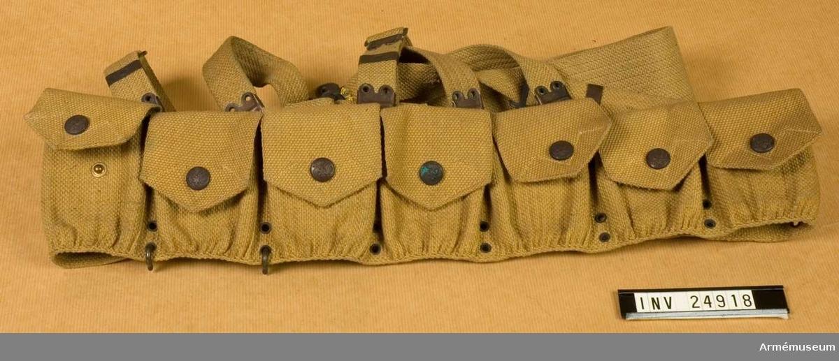 """Samhörande nr 24918-9, patronbälte, gehäng. Grupp C II. Nio cm brett bälte av tjockt bomullstyg, """"wibbing"""" med  järn-pännen och beslag på ändarna. Nio stycken patronväskor av samma tyg, med lock som stänges med järnknappar, d:15 mm, med amerikanska statens vapen - sköld och örn - för fem patroner i varje.  LITT  Arméen Album III. Die Armee der Vereinigten Staaten von Amerika. Von de Witt Clinton Falls. Verlag von M. Ruhl. Leipzig Bilaga. Sida 4. """"Kadett. Felduniform"""", första i raden. Kadett med fältutrutsning med samma patronväskor. Soldiers of the American Army, Fritz Kredel. Frederick P Todd. 1775-1954. Henry Regnery Company Chicago Plate 27 Staff and Pioneer. Infantry, A.E.F. 1918. """"Pioneer in full fieldkit"""". Patronväska liknande väv.Enl kapten Granberg."""