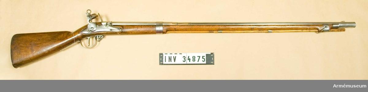 """Grupp E II.  Projekt för infanteriet; av Blix i Söderhamn 1690-talet.  Kammarstycket är 31,4 cm långt, baktill åttkantigt, men framtill på en längd av 2 cm sextonkantigt. Det avslutas längst fram av en insvarvad och en upphöjd rand. 4,7 cm framför den sistnämnda på åter ett par dylika ränder kring det runda, långa fältet och 0,5 cm längre fram åter ett par. Ett kraftigt avlångt korn sitter 4,2 cm bakom pipmynningen och längst fram på svanskruvsstjärten finns ett ovanligt kraftigt, lågt ståndsikte. På kammarstyckets översida framför  siktet finns en kronstämpel och siffran 2 och på vänstra sidan sitter en egendomlig stämpel, vilken ser ut som ett monogram mellan 2 och C. På pipans undersida 7,8 cm bakom mynningen finns en kraftig, skarpkantig fläns eller klack, vilken på båda sidor blir lägre uppåt och som går upp på pipan bägge sidor litet högre än vad framstocken gör. Pipan har 3 häften och korsskruven går nedifrån.  Låset har varhake, Blecket är kullrigt samt baktill utdraget i en spets. Hanhalsen är baktill plan och läppskruvsringen har en diam, av 1,9 cm. Pannskruven ersättes av en nit, eldstålsfjäderns skruv går utifrån och samma fjäders bukt går framför den främre låsskruvens ände. Pannstjärten är kort. På bleckets utsida står """"M. Blix Söderhamn"""".  Stocken är av al och har kräva. Framstocken slutar 8,5 cm bakom pipmynningen. Stocken har varit spräckt i kolvhalsen, men är nu hoplimmad.  Järnplåtsbeslagen bestå av bakplåt, som fasthålles av stift; stor varbygel, vars bakre arm fasthålles av två stift och vars främre, som längst fram är utbildad tlll en ögla, fasthålles av korsskruven; kort avtryckarebleck, som fasthålles av 2 stift; ett 2,6 cm brett järnband, som går kring pipans och framstockens 22,9 cm framför pipans bakre ände; ett platt, s-formigt sidbleck; två släta rörkor; ett krävbeslag om 2,3 cm bredd samt ett näsbleck av samma storleck. Den nedre rembygeln är fäst i varbygeln ögla, men den främre, u-formiga, fasthålles av en skruv, vilken går genom kräv"""