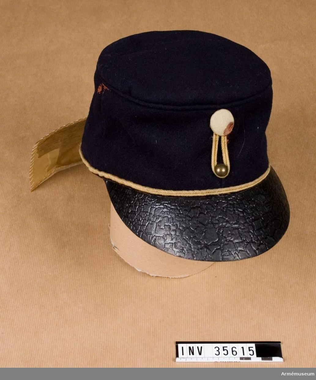 """Grupp C I. Mössa enligt go 24/10 1860, armén allmänt. Modellapp. Ur släpuniform för manskap vid Göta artillerireg. Livplagg m/1845. Består av kappa, epåletter, byxor. Mössa av mörkblå kläde med gul passpoal. Skärm av läder. Vitt kompanimärke. Fodrad med grått linne och vaxduk. Vidhängande trasig modellapp: """"Modell å Lägermössa (...) skeende anskaffning (...) behof. Likheten med den af (...) Modell, intygar: (oläslig underskrift). Baksidan: """"af: Mörkblått kläde, 1 1/2 fot bredt (?) fot. Foderväf, grå, 2 fot bred (?) fot. (?) snören, gula =2, (?). (?) till mösskullen = 1 (?). (...)kullriga, mässings, små =1/12 (?)."""""""