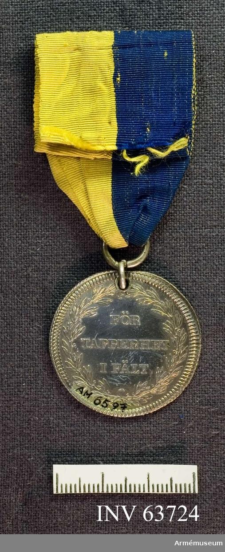 Grupp M.  Frånsidan: Text inom en lagerkrans. Medaljens kant strierad på båda sidor, randen slät.                       Åtsidan: Utan inskrift. Svärdsordens riddarstjärna under kunglig krona.  Karl XIII.