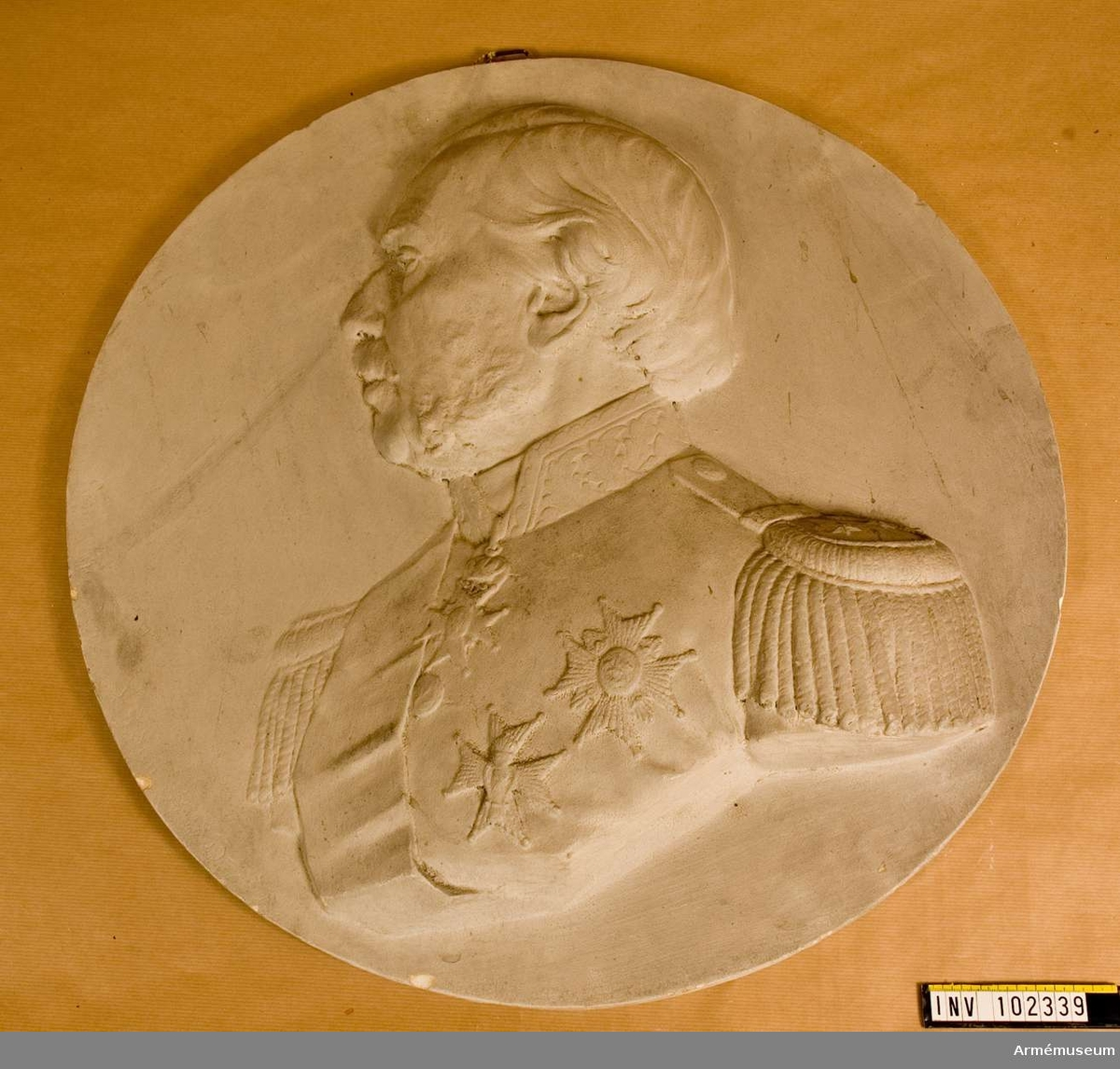 Grupp M I. Porträttmedaljon föreställande löjtnanten m m greve Gustaf Sandels f. 1815 d. 1915. Sandels är porträtterad i bröstbild åt vänster. Klädd i uniform har han generallöjtnants gradbeteckning, stora bandet av svärdsorden samt kraschaner. Huvudet är bart. Material: gips.