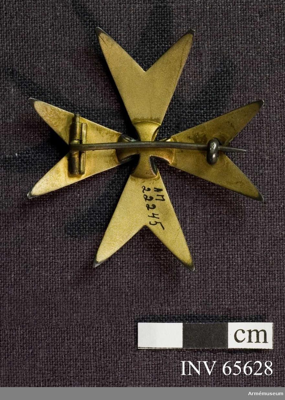 Grupp M II. Åttauddigt kors av vit emalj. På frånsidan ett S:t Georgekors i samma material som resten av frånsidan (-som förstärkning av ordenskorsets mittpunkt?).