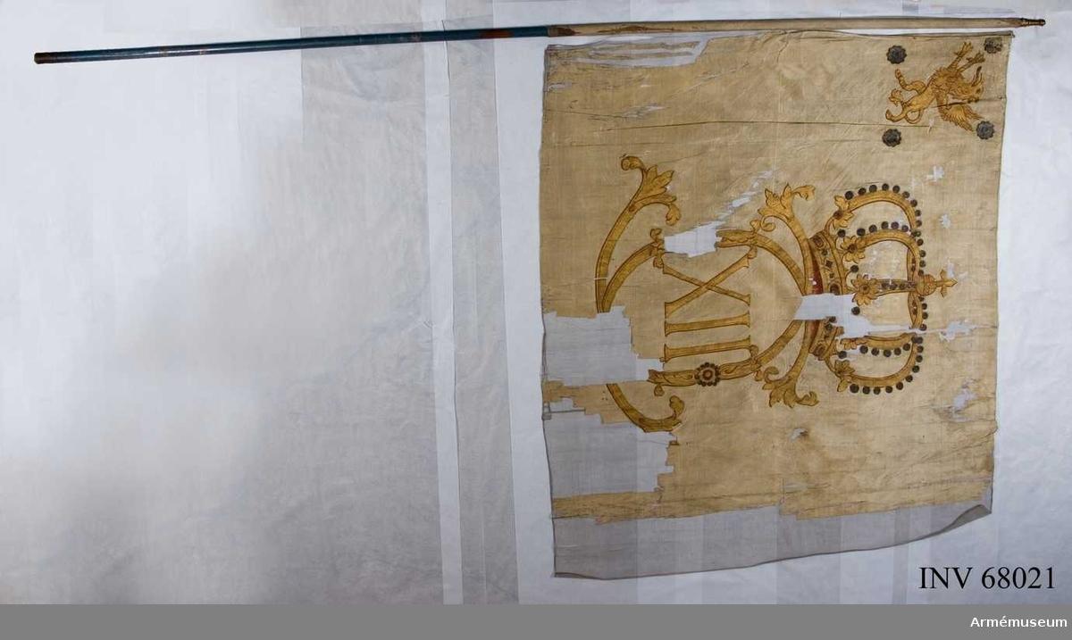 Duk: Tillverkad av enkel vit sidentaft, sydd av två horisontella våder. Duken fäst med en rad tennlickor på ett vitt sidenband.   Dekor: Målad endast på utsidan Karl XII:s namnchiffer, stort dubbelt C inom detta XII, under en stor sluten krona med kronfoder i rött samt pärlor i silver. Namnchiffret och kronan i guld med röda konturer.   I övre inre hörnet målat omvänt lika Östergötlands sköldemärke, en gyllene grip med konturer i rött, omgiven av fyra stycken silverrosor.   Stång: Tillverkad av blåmålad furu.  Holk av förgylld mässing.