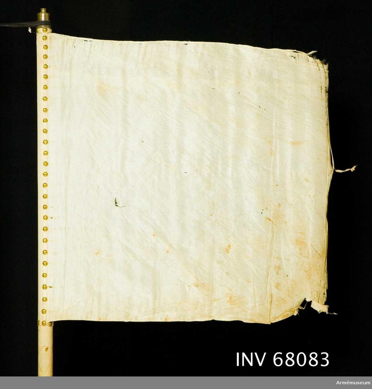 Duk: Tillverkad av enkel, vit sidentaft. Fållen lagd åt dukens utsida. Duken fäst med en rad tennlickor på ett vitt mönstervävt band.   Dekor: Saknas.  Stång: Tillverkad av trä, vitmålad, smal. Holk av mässing.  Skinnremmar:  En övre, vit skinnrem fäst vid stången på 690-710 mm längd mätt från dukens nedre fäste, bildar en 660 mm lång ögla; mätt, bildar en 260 mm lång ögla.