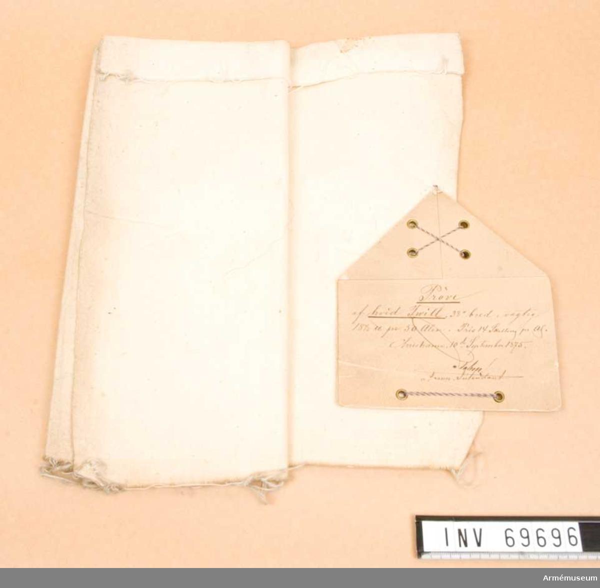 """På etiketten står skrivet: """"Pröve af hvid twill, 38"""" bred, vogtig 18 1/2 u pr 50 alen. Pris 14 skilling pr as. Christiania, 10de September 1875."""""""