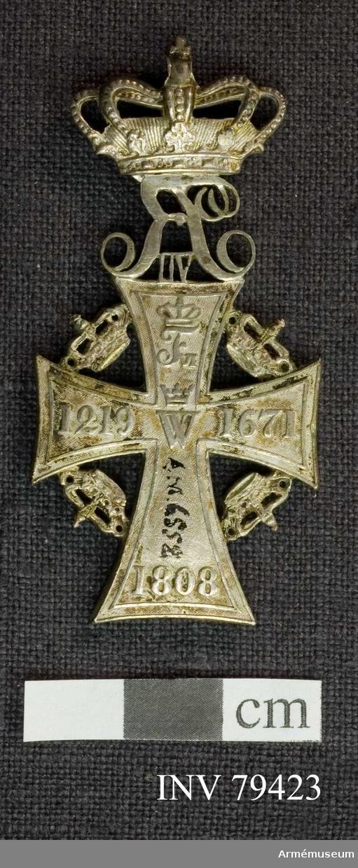 """Grupp M  Åtsida: Ett silverkors med inskriptionen (i upphöjda bokstäver) lika fördelad på korsets armar. Högst upp R VII. Jämsides med ytterlinien löper en smal, upphöjd rand, i mitten """"C5"""" under kunglig krona.   Mellan korsets armar äro placerade kungliga kronor i en cirkel; ovanpå äversta armen """"R VIII"""" under kunglig krona.  Frånsidan: Samma utseende som åtsidan utom att """"R VII"""" står bakfram och inskriptionen är en annan.  På korsets översta arm """"F VI"""" under kunglig krona, på venstra armen: 1219, på högra armen 1671 och på den nedersta 1808, i korsets mitt: W under en krona.  Beskrivning: Carl Peyron."""