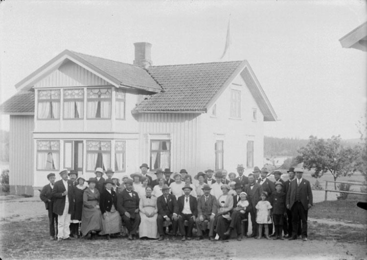 """Enligt noteringar: """"19 juli 1921. Frisinnade föreningen på sommarmöte hos Anders Pettersson på Elseröd. Färden till mötet företogs delvis med roddbåt från Kaserna i Munkedal. Några av personerna identifierade: Rad 1: nr. 6 Anders Pettersson, Elseröd (i vit väst). Rad 2: Sören Grundberg (ung man i svart skärmmössa). nr. 2 från vänster i vit skärmmössa troligen stationsmästare A.H. Svahn. Längst till höger Axel Sohlberg (klädd i keps) Bakersta raden: nr. 8 skogvaktare Albert Eriksson (hatt och mustasch), Melker Hansson."""" (BJ)"""
