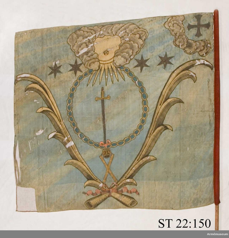Duk av blå kinesisk sidendamast. I dukens övre del ett moln som omgärdar ett öga i ett gyllene fält. Under molnet ett svärd inom den ryska St Andreas orden i målad guldkedja. Allt inramas av palmblad i halmgul sidendräll nedtill hopknutna med rosa band. I stångsidans övre hörn ett kors inom ett moln. Fyra gyllene stjärnor markerar vilket kompani fanan hör till. Strumpa av rött kläde. Stången avkortad.