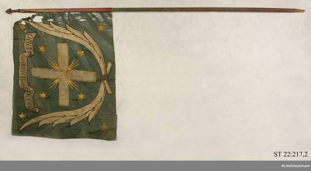 """Duk av grön sidendamast med infälld och målad dekor bestående av ett kors omgärdat av palmblad i vit sidendamast. I ett textband rysk text betydande """"I detta tecken ska du segra"""". Strumpa av rött ylle. Slät, grönmålad stång. Spetsen bevarad."""