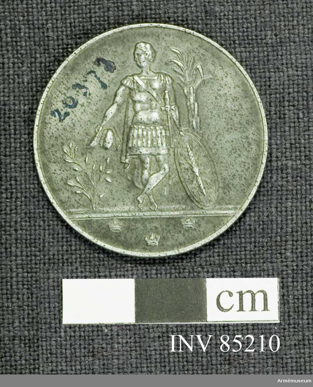 Grupp: M.  Åtsidan:. Överst, friliggande: en stor kungl. krona; därunder två medelst ett band förenade i kors lagda, stiliserade bladknippen, delvis vilande på, delvis trädda igenom en medaljens nedre del upptagande lagerkrans. Frånsidan: En med benen i kors stående romersk krigare, sedd framifrån med huvudet vänt åt höger, håller i den halft utsträckta högra armen hjälmen och med den venstra en oval snett lutande, på marken vilande sköld; bakom synes ett högt majspalm? stånd; på marken en olivbuske. Under avskärningen: 3 kronor.. Beskr. Prn. Minnestecknet utdelat såsom tack för de bidrag, som lämnats till restaurering av Karlbergs slott. .har jag härmed äran översända den  minnesjeton, som präglats till minne av Kongl. krigsakademiens och Kungl. krigsskolans 150-åriga tillvaro. Karlbergs slott den 20/12 1941. Bertil G. Uggla (undertecknat) Chef för Kungl. krigsskolan.