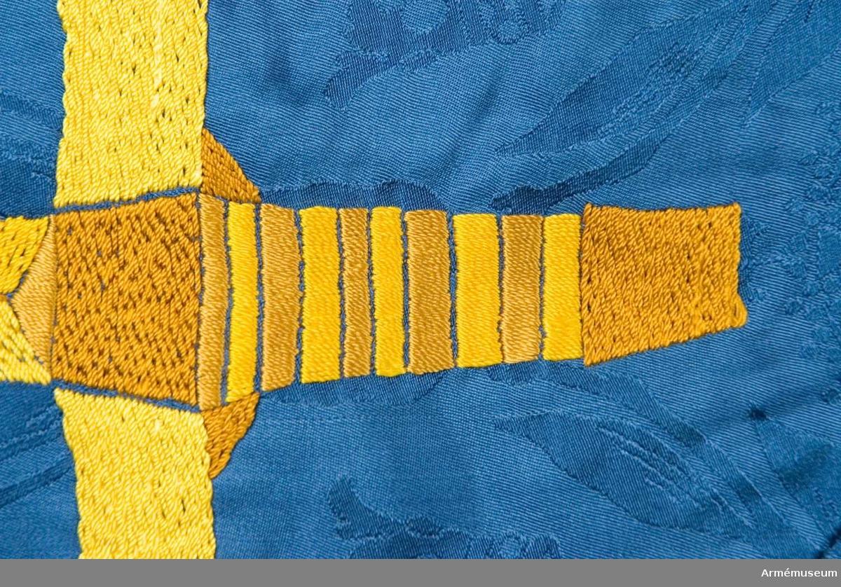 På blå duk ett stolpvis ställt gult svärd, i övre inre hörnet ett med öppen krona krönt upprest gult lejon. Duken av damastvävt fansiden. Motivet handbroderat i intarsia. Tillhörande spets, skyddsduk och fodral. Sidenet vävt av Almgrens sidenväveri