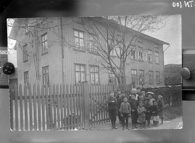 """Enligt senare noteringar: """"Avfotografering av äldre foto: barn framför bostadshus vid """"Svarta vägen"""", """"Viggero"""", ägare: Tändsticksfabriken."""""""