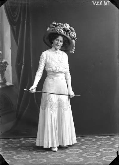 """Enligt senare noteringar: """"Ateljéfoto av en kvinna, med vit klänning, stor hatt med blommor samt käpp."""""""