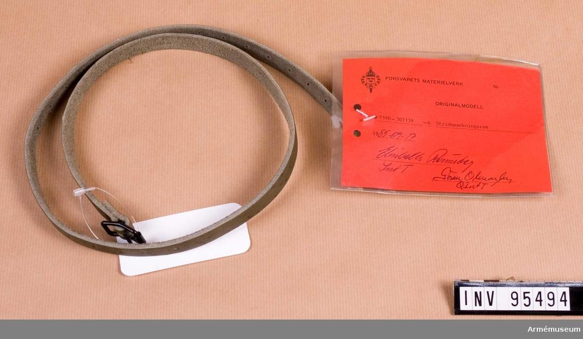 """Vidhängande etikett: """"Försvarets materielverk Originalmodell M 7390-301139-6, Stridspackningsrem, 1985-09-17 (oläslig underskrift)""""."""