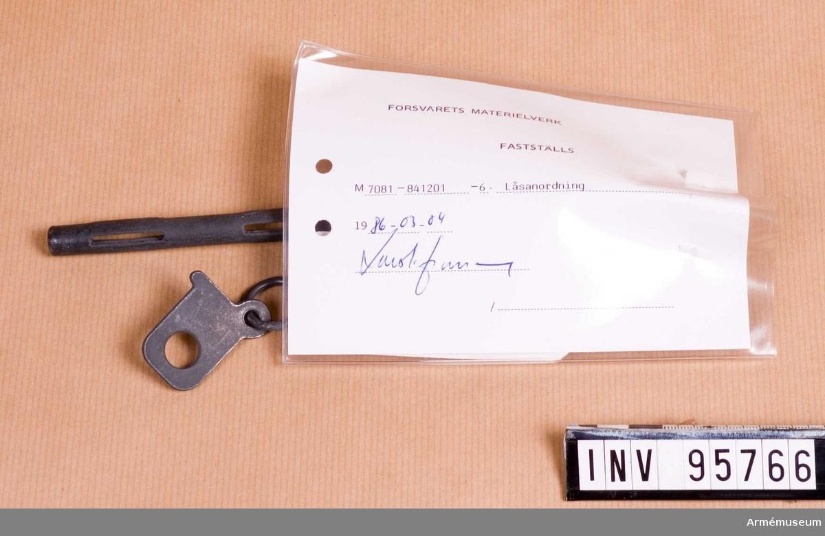"""Vidhängande etikett: """"Försvarets materielverk Fastställs M 7381-841201-6, Låsanordning, 1986-03-04 (oläslig underskrift)""""."""