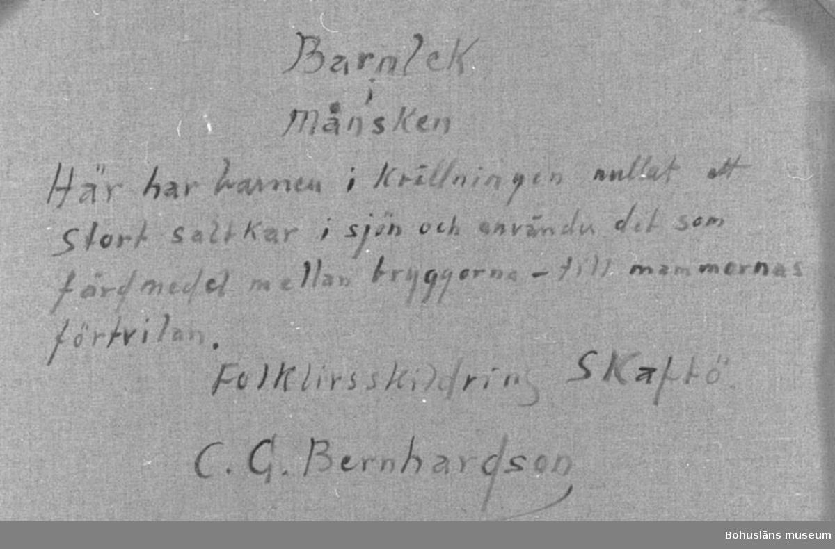 """Montering: ram. Baksidestext:  Barnlek i månsken.  Här har barnen i Kvällningen rullat ett stort saltkar i sjön och använder det som färdmedel mellan bryggorna - till mammornas förtvivlan. Folklivsskildring Skaftö. C.G. Bernhardson.""""  Ordförklaring: Saltkar = kar, oftast stort laggkärl, för insaltning.  Litteratur: Bernhardson, C.G.: Bohuslänskt folkliv, Uddevalla, 1982, sidan 248.  Titel i boken: Tilltag. Här gorma gummorna över ungarnas tilltag att rulla det största saltkaret i sjön och leka rutebåt på grunt vatten mellan bodarna. Sådant fick man inte göra och det gällde för barnen att kvickt landa på en för gummorna olämplig plats. Tidsbild 1920-talet.  Ordförklaring: Rutebåt = båt som trafikerade en viss route, rutt, d.v.s. fastlagd färdväg.  Övrig historik; se CGB001"""