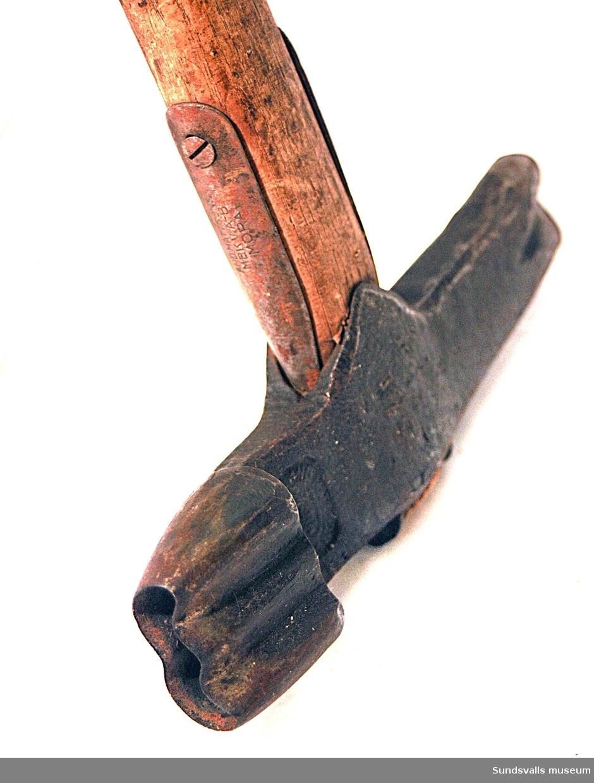Märkyxa med träskaft. Huvudet mäter 19,5 cm och har huggmärken som, enligt en förteckning över timmermärken i Indals älvs och Ljunga älvs allmänna flottleder, ska stå för Nyhamns Aktiebolag.