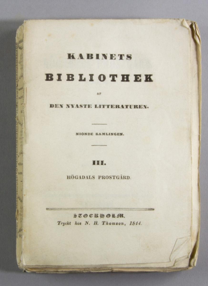 """Bok, häftat pappersband: """"Högadals prostgård. Del I"""" skriven av Wilhelmina Gravallius och tryckt hos N. H. Thomson i Stockholm 1844.   Första häftet av två. Häftad och oskuren i tryckt omslag."""