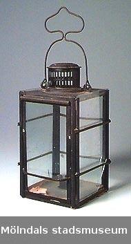 Fyrkantig lykta i svart plåt med handtag och rund ventilationstrumma med galler upptill. Fyra glas, delvis spruckna. Inuti finns en hållare för stearinljus. Rester av rött stearin. Höjd med handtag: 365 mm.