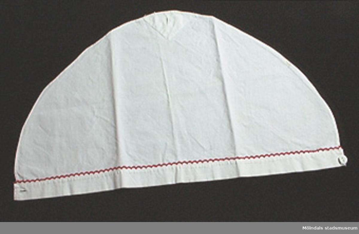 Snibb i form av triangelformat tygstycke, som knäpps med en tygklädd knapp. Längs framkanten finns en röd broderad bård.