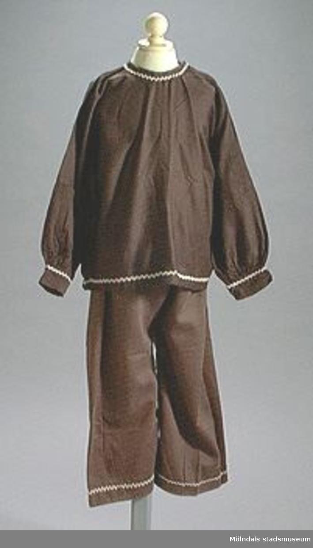 Blus med byxor. Brunt bomullstyg. Mått för byxorna: L 690 mm, B 440 mm. En av blusarna är mörkbrun.Kring nederkant, halslinning och ärmar på blusen finns ett påsytt vågformat band. Samma slags band finns nedtill på byxbenen. Kläderna har använts för barn som skall utklädas till pepparkaksgubbar.Tidigare sakord: blus.