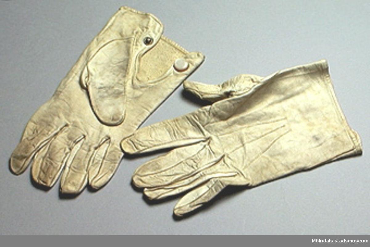 Vita korta damhandskar i nappa. Knäppes med tryckknapp vid handleden.