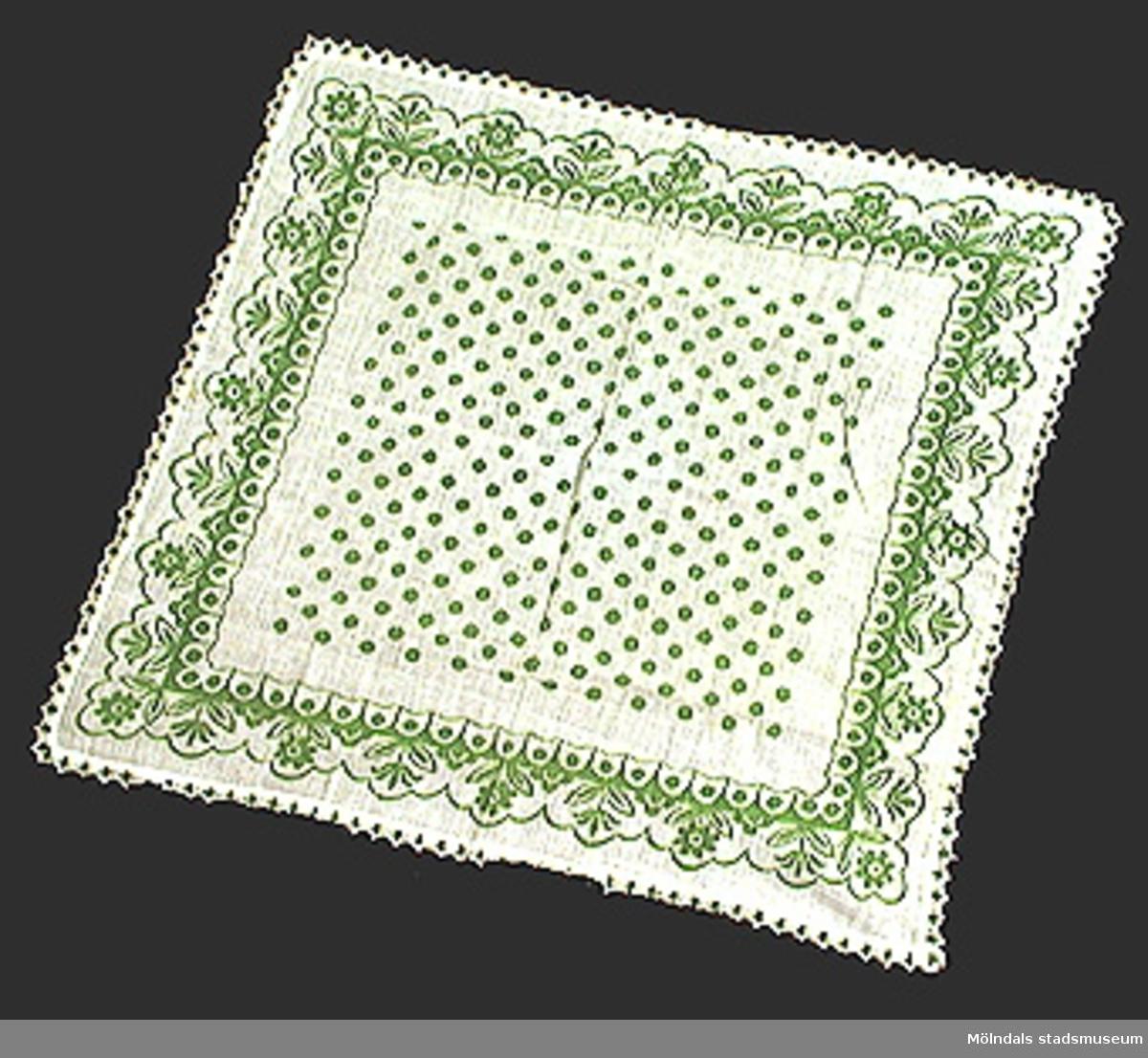 Vit bomullsduk med tryckta gröna prickar, samt grön mönsterbård och grön/vit spets runt om.