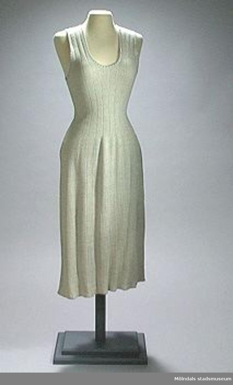 Ärmlös, ljugrå underklänning med axelband. Ingen egentlig urringning. Något utställd kjoldel. Tyget är elastiskt på tvären, eftersom det är resårstickat.Ryggbredd: 300 mm.