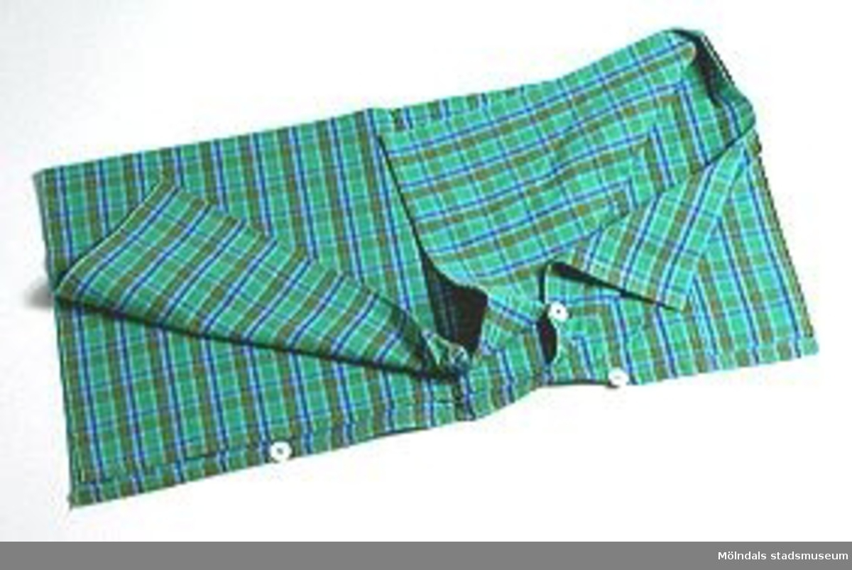 Påslakan i grönrutigt tyg med knappar. Tillhör MM02510 - 02512 (påslakan och kuddvar).