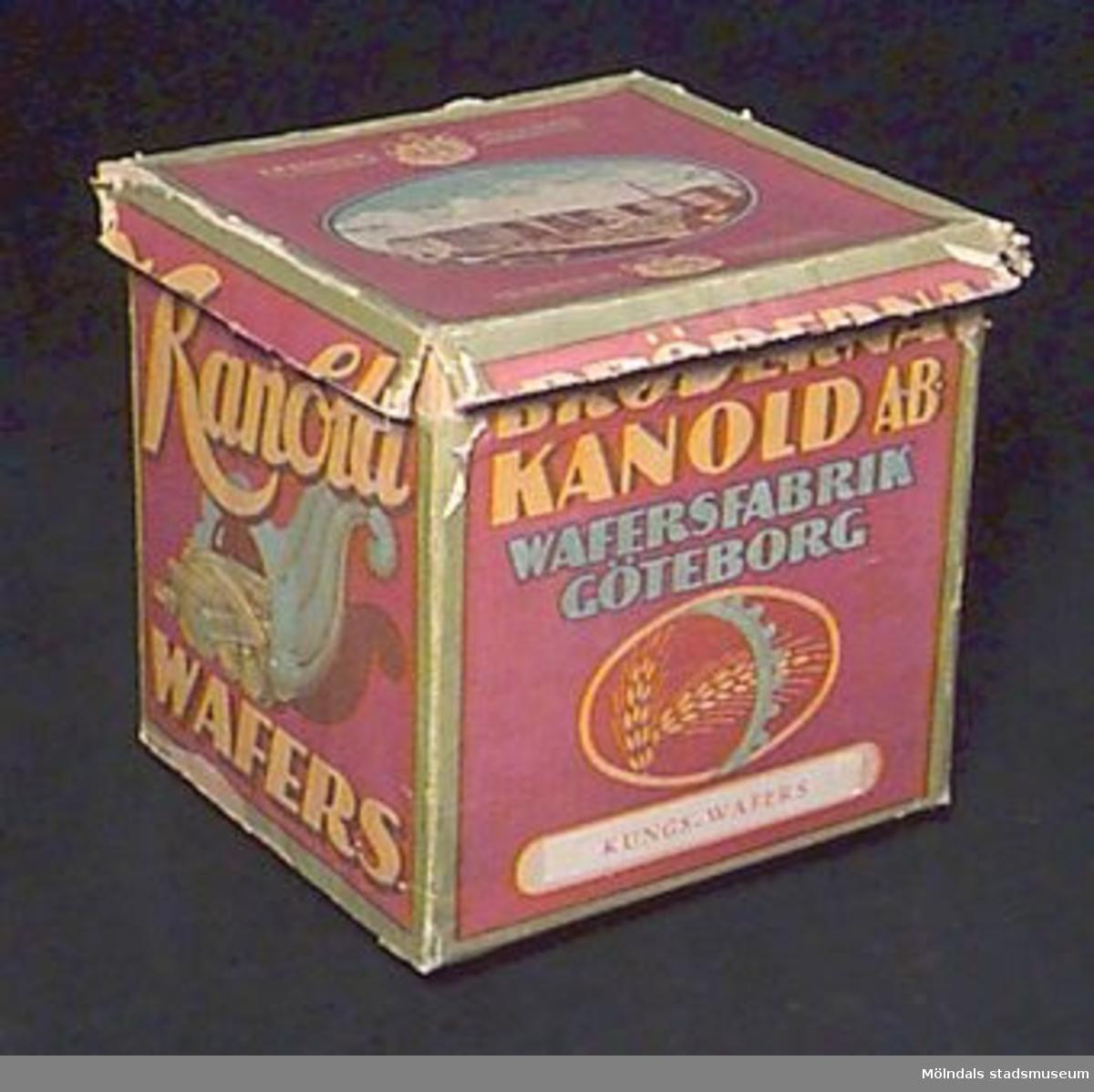 """Pappkartong med polykromt papper och huvudsaklig färg lila, text i gult. På fram- och baksida text: """"BRÖDERNA KANOLD AB WAFERSFABRIK GÖTEBORG"""". Påklistrad papperslapp med tryck: """"KUNGS-WAFERS"""". Bild med sädesax och del av kugghjul, kortsidorna har texten """"Kanold WAFERS"""" och ett ymnighetshorn med Kanolds produkter. På locket foto över fabriken, stora riksvapnet avbildat två gånger och text: """"HM Konungens hovleverantör"""" och """"H.K.H. Kronprinsens hovleverantör"""". Papperet tillverkat av AB Vaxpapper & Lito, Göteborg, troligen också kartongen. AB Vaxpapper & Lito var dotterbolag till AB Bröderna Kanold. Beräkningar med blyerts på locket."""