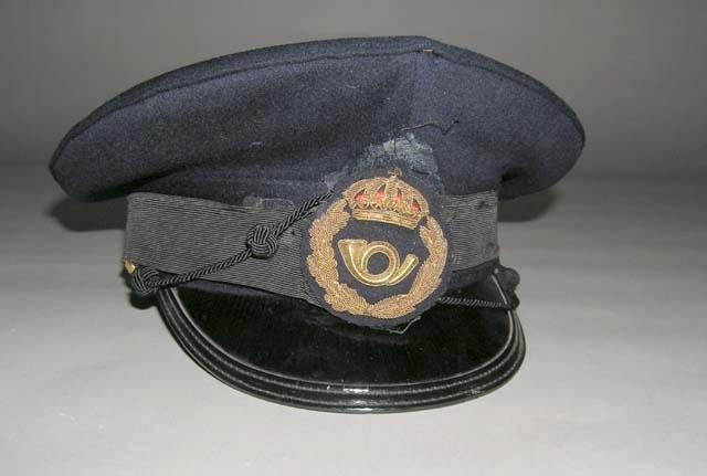 Uniformsmössa av mörkblått kläde med skärm och mössmärke.Mössmärket är fastlimmat och har delvis lossnat. Märket är förtjänstemän i lönegrad A10 - 12.