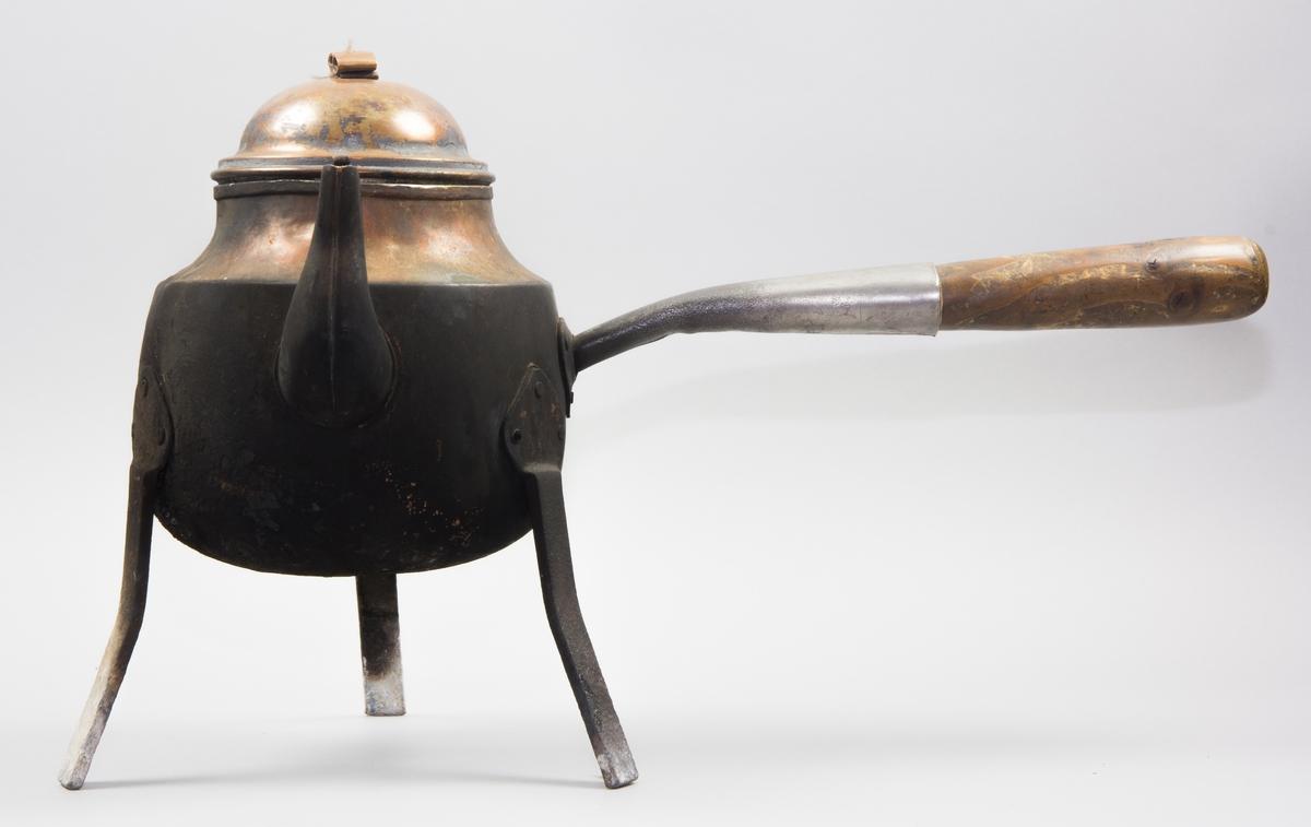 Kaffepanna tillverkad  av koppar. Tre ben av järn, hjärtformade fästen, nitade. Handtag av järn med förlängning av trä. Lock med fals som ligger inuti pannan, knopp av rullad plåtbit. Svängd pip med fäste för lövformat lock, detta lock har dock förkommit. Förtent insida.