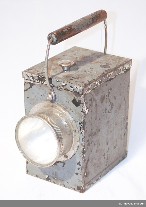 Batteridriven handlykta i plåt med trähandtag. Målad i svart, sedan grått. Fastskruvat lock upptill. Användes på Wiiforsens Kraftstation.