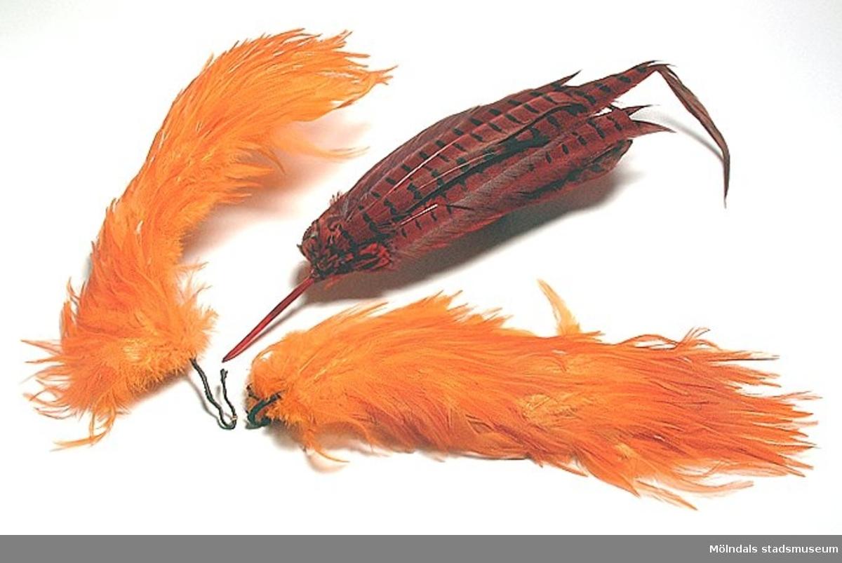 Fjäderarrangemang i orange, förmodligen klänningsdekorationá la 1920-tal.
