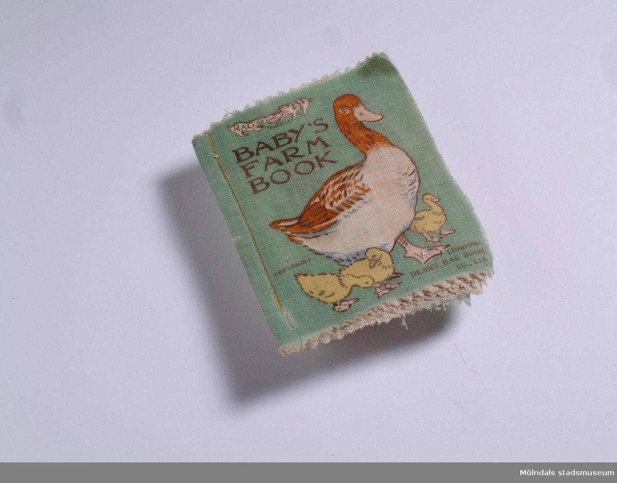 Babybok i tyg med tryckta djurmotiv. Engelsk text.Titel: Baby's Farm book. Brukaren är född och uppvuxen i Mölndal.