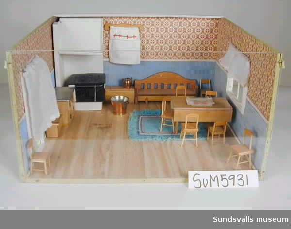 Dockskåpskök omgiven på tre sidor av träväggar med ett fönster och en dörr, den fjärde väggen av plexiglas. I ena hörnet en vedspis med spiskupa och spiskrok. Rummet är möblerat med ett bord med bordsduk och åtta stycken stolar, en matta, en soffa, två vedlårar, en kopparkittel, en kopparhink, diskbänk, ett par gardiner, en paradhanduk och ett draperi. 8 stolar, 1 bord, 1 duk, 1 matta. 1 soffa, 2 vedlådor, 1 kopparskittel, 1 kopparhink, 1 diskbänk, 1 par gardiner, 1 gardinkappa. 1 paradhandduk, 1 spis, ved + spiskåpa, 1 spiskrok