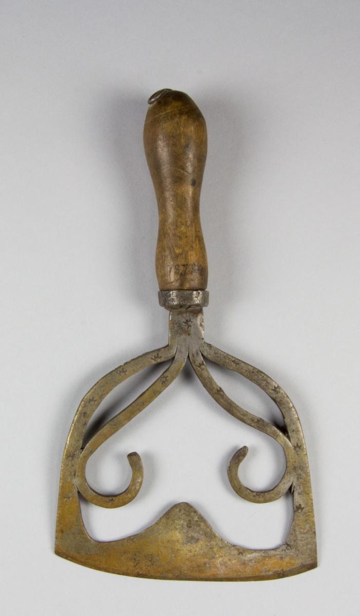 Hackkniv av stål och trä. Svarvat handtag av trä och bygelformat knivblad, dekorerat med stämplade stjärnor, monterat i handtaget med hjälp av en ring av järn. Dekorsmide i det genombrutna hålet i knivbladet.