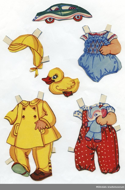 """Pappdocka med kläder och tillbehör från 1950-talet. Docka och kläder är märkta """"Karl Gustav"""" på baksidan - dockans namn. Dockan föreställer ett litet barn, iklädd tygblöja, strumpor och skor. Garderoben består av lekdräkt, sparkdräkt, """"stickade"""" plagg, pyjamas, samt regnkläder med tillhörande huvudbonad. I materialet finns också tillbehör, såsom bil, anka, boll och tandborste i glas. Docka och kläder förvaras ihop med annan pappdocka (MM 04660), i brunt kuvert märkt """"Karl Gustav"""" och """"Nalle Björn"""". Ursprunligen kommer kuvertet från Familjebidragsnämnden för Göteborgs stad, poststämplat 1955. Familjebidragsnämnden gav ekonomiskt stöd till familjer där försörjaren var inkallad i det militära, från ca 1940 och framåt, in i 1960-talet."""
