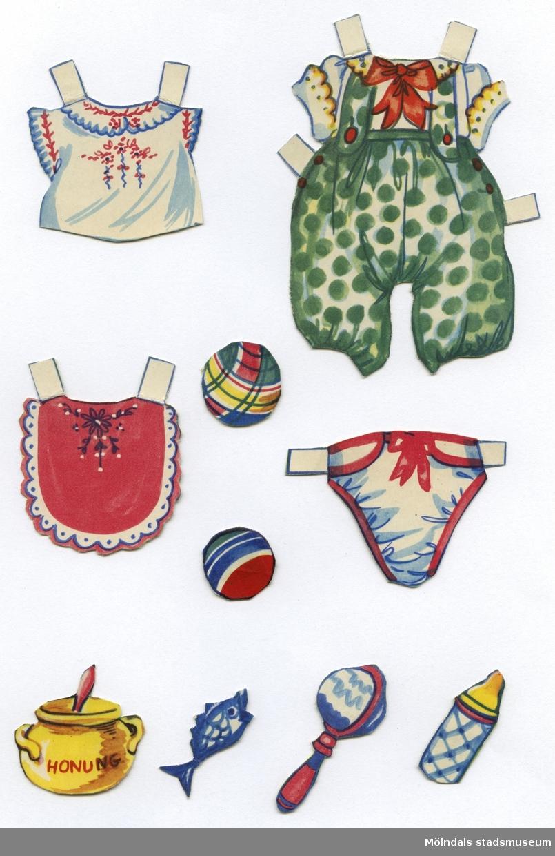 """Pappdocka med kläder och tillbehör från 1950-talet. Docka och kläder är märkta """"Nalle Björn"""" på baksidan - dockans namn. Dockan föreställer en leksaksbjörn. Garderoben består av lekdräkter, sparkdräkter, """"stickade"""" plagg och en blus. I materialet finns också tillbehör, såsom hakklapp, honungsburk, tygblöja, nappflaska och bollar. Docka och kläder förvaras ihop med annan pappdocka (MM 04659), i ett brunt kuvert märkt """"Karl Gustav"""" och """"Nalle Björn"""". Ursprungligen kommer kuvertet från Familjebidragsnämnden för Göteborgs stad, poststämplat 1955. Familjebidragsnämnden gav ekonomiskt stöd till familjer där försörjaren var inkallad i det militära, från ca 1940 och framåt, in i 1960-talet."""