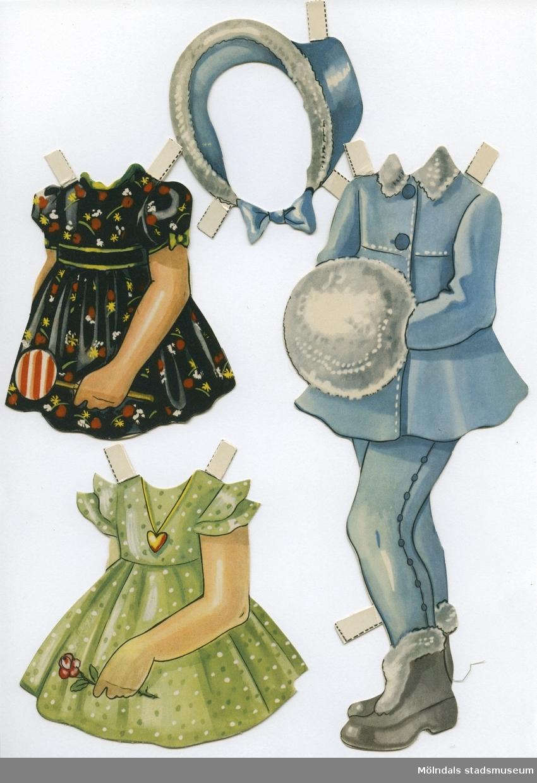 """Pappdocka med kläder från 1950-talet. Docka och kläder är märkta """"Karin"""" på baksidan - dockans namn. Dockan föreställer en flicka med blond frisyr och blå ögon, iklädd underklänning, nylonstrumpor med strumpeband och skor. Garderoben består av tre klänningar, varav en med matchande mössa, kappa och kjol med basker, samt vinterkappa med byxor, pampuscher (galosch med pälsbräm), muff och hatt. Docka och kläder förvaras i en avlång påse av smörpapper, med texten """"Påklädningsdockan 'Karin'""""."""