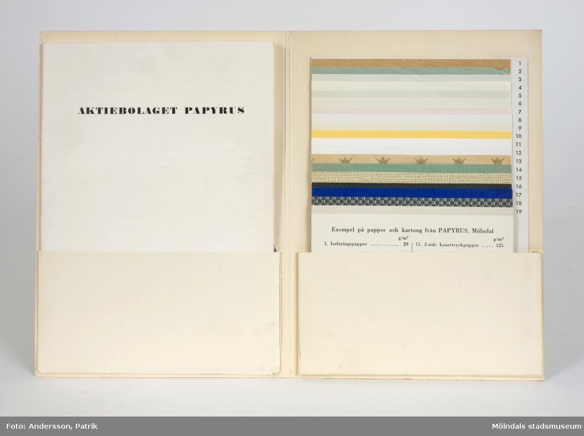 """Benvit pappmapp, med texten; """"Papyrus, Aktiebolaget Papyrus, Mölndal"""", samt Papyrus emblem med sfinx på fundament på framsidan, från 1953.Inut finns två fack. Det vänstra innehåller ett häfte med titeln """"Med tack för Edert besök"""". Häftet har en kortfattad beskrivning av verksamheten på Papyrus i text och bild, och inleds av en kort historik. Det högra facket presenterar nitton """"Exempel på papper och kartong från Papyrus, Mölndal"""", i lättöverskådligt provhäfte."""