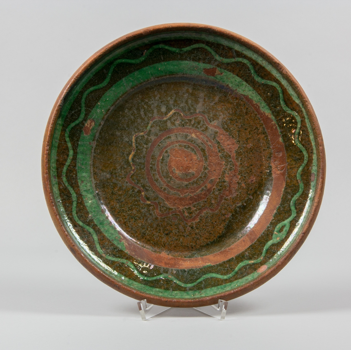 """Fat av blyglaserat lergods. Dekorerat med våglinje mellan två breda bårder i grönt. Gröntonad blyglasyr över ovansidan, undersidan oglaserad. Uppstående brätte, eller brämkant. I spegeln våglinje runt spiral. Stämpel på undersidan: """"Wernamo Johansberg""""."""